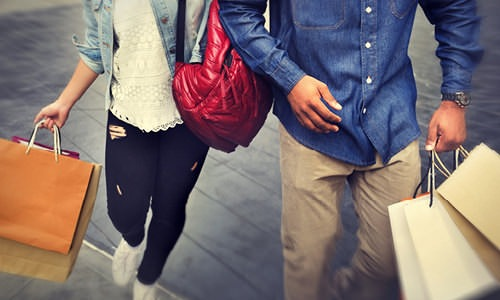 guy and girl walk down the side walk with shopping bags in their hands